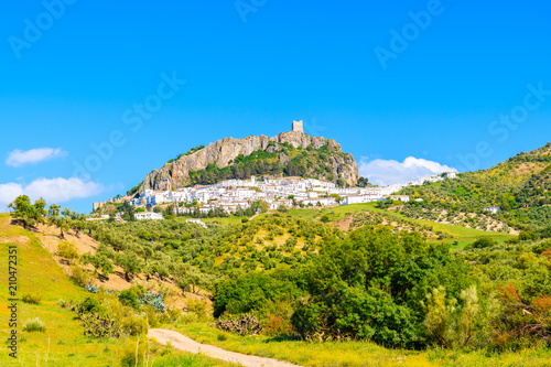 Fotomural White village of Zahara de la Sierra on green hills at spring time, Andalusia, S
