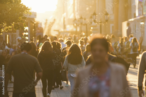 fototapeta na ścianę Silhouettes of people crowd walking down the street at summer evening, beautiful light at sunset