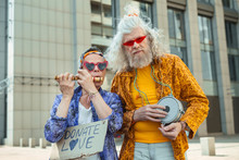 Donate Love. Two Elderly Hippy Men Wearing Shining Bright Clothes Encouraging People For Donating Love