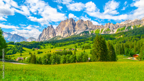 Fototapeta Rocky ridge of Pomagagnon Mountain above Cortina d'Ampezzo with green meadows and blue sky with white summer clouds, Dolomites,, Italy. obraz