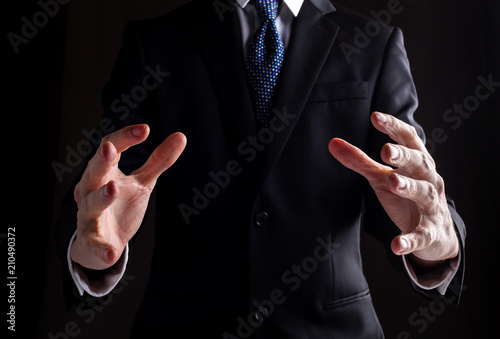 Photo  Man in a business suit holding his hands out and showing something