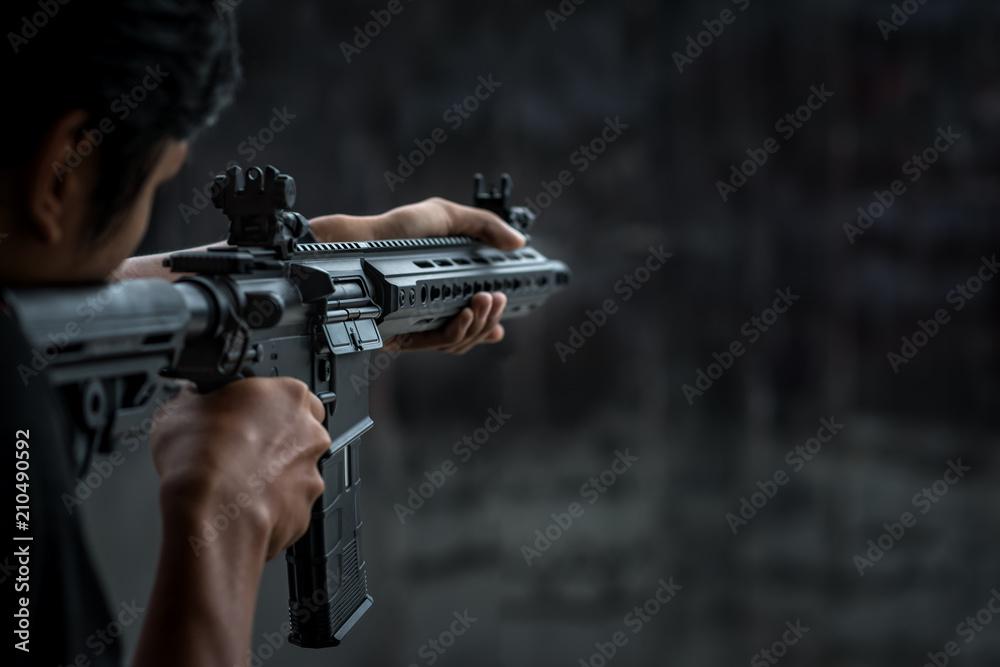 Fototapeta Man holding gun aiming pistol in shooting range