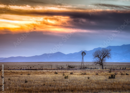 Old windmill at sunset with a dead tree next to it. The Rocky Mountains can be seen in the background,