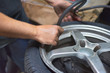 Closeup Of Mechanic At Repair Service Station inflating Tyre.