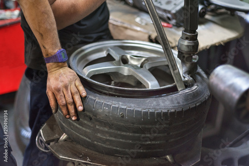 Professional mechanic using machine for tyre change.