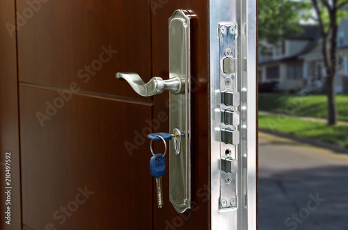 Fototapeta Open door of a family home. Close-up of the lock with your keys on an armored door. Security. obraz