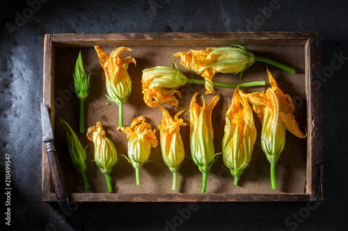 Ingredients for tasty roasted zucchini flower in wooden box