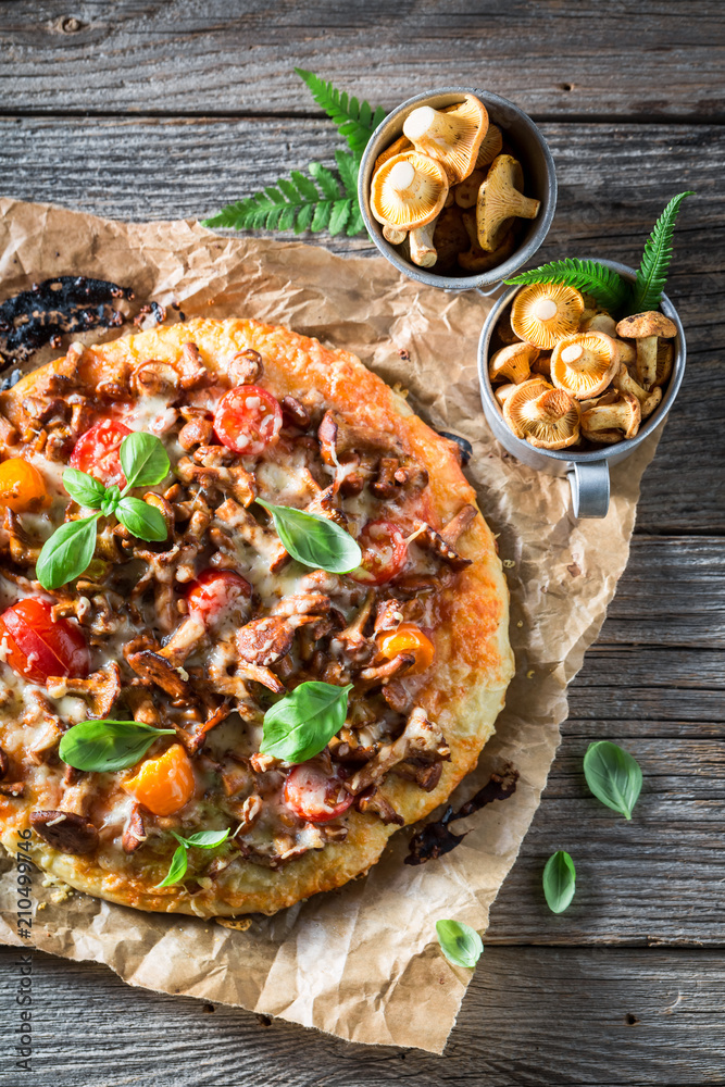 Tasty and homemade pizza made of noble mushrooms and tomatoes