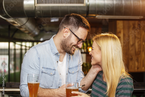 Young couple looking each other in local pub with glass of beer Poster