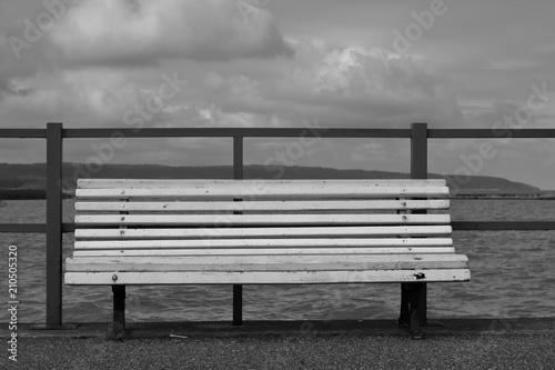 Pusta drewniana biała ławka stoi pusta na brzegu jeziora (nabrzeżu morza), za nią niska metalowa barierka, w tle woda, horyzont, chmury na niebie, czarno-białe