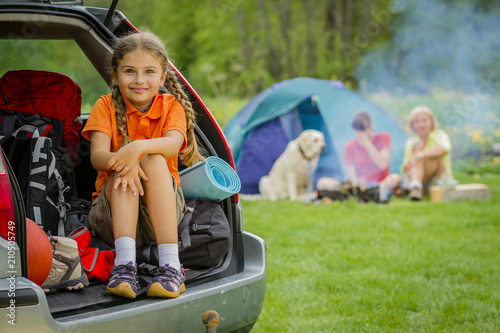 Keuken foto achterwand Kamperen Happy young girl in car near his camp tent at green field