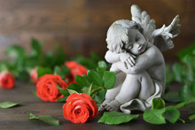 Angel Guardian And Roses On Wooden Background