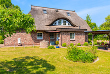 SEEDORF VILLAGE, RUEGEN ISLAND - MAY 28, 2018: Garden With Traditional Thatched Roof House Near Seedorf Village, Baltic Sea, Germany. Rugen Is Popular Tourist Destination Due To Its Rural Landscape.