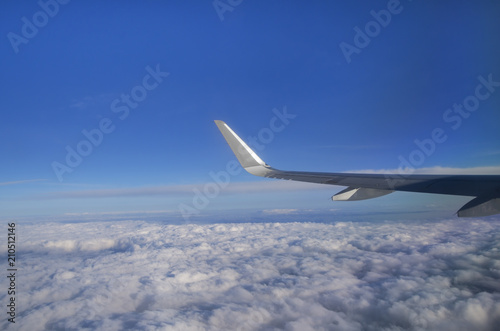Photo View from airplane window with silver wing, blue sky, white clouds and horizon;