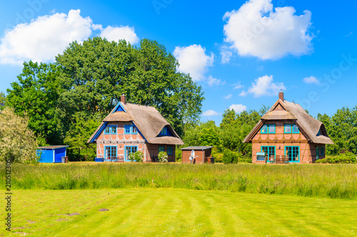 Traditional thatched roof house on green meadow in Gross Zicker village on sunny summer day, Ruegen island, Baltic Sea, Germany
