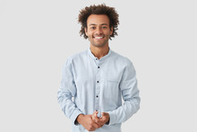 Horizontal Shot Of Happy Mixed Race Male With Shining Smile, Feels Glad As Recieves Bonus And Praise For Good Work, Has Specific Appearance, Afro Hairstyle, Dressed In Fashionable White Shirt