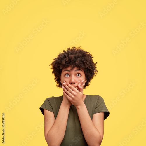 Fototapeta Vertical portrait of emotional scared African American female closes mouth with palms, looks with frightened expression upwards, tries not to make any sound, isolated over yellow background. obraz na płótnie