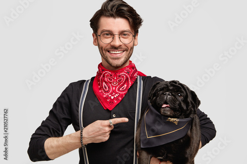 Obraz Handsome stylish male vet points at his black pug dog, wears spectacles, has happy expression, poses against white blank wall. Lovely pet in hands of host. Friendship and pedigree animals concept - fototapety do salonu