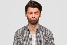 Funny European Male Makes Grimace, Purses Lips And Crosses Eyes, Foolishes Indoor, Has Fun, Dressed In Fashionable Shirt, Isolated Over White Background. People And Facial Expressions Concept
