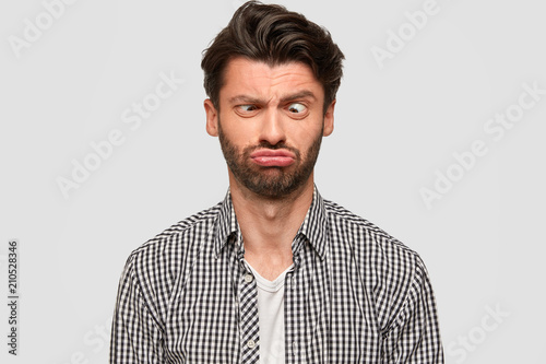 Fototapeta Funny European male makes grimace, purses lips and crosses eyes, foolishes indoor, has fun, dressed in fashionable shirt, isolated over white background