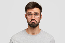 Headshot Of Attractive Young Male With Beard, Purses Lips, Feels Puzzled, Has Hesitant And Miserable Look, Being Disappointed And Displeased, Dressed Casually, Isolated Over White Background.