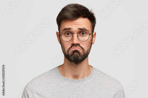 Photo Headshot of attractive young male with beard, purses lips, feels puzzled, has hesitant and miserable look, being disappointed and displeased, dressed casually, isolated over white background