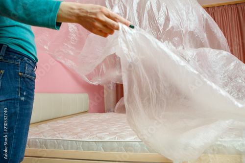 Photo of young woman covering bed with polyethylene