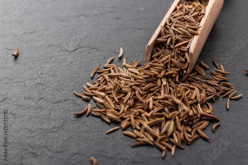 Fototapeta Seeds of cumin on a dark stone background obraz