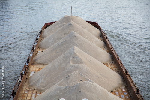 Canvas A barge with sand floats along the river