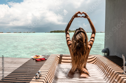 Foto  sexy girl  with white towel on her body relaxing on Maldive's villa outdoor bath