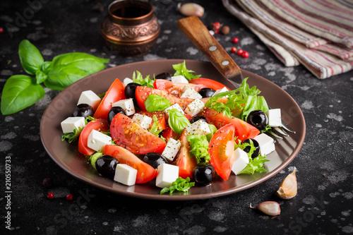 Fototapeta Salad with tomatoes, feta, olives and Basil, serving on a dark background obraz