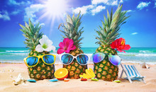Attractive Pineapples In Stylish Sunglasses On The Sand Against Turquoise Sea