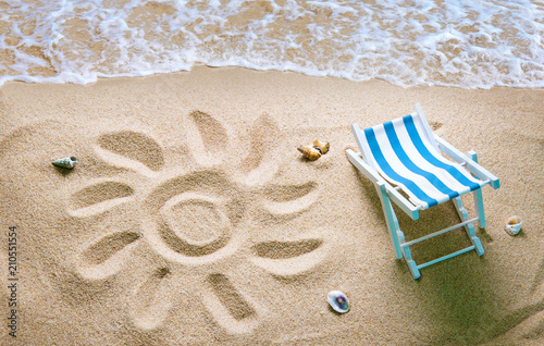 Foto op Canvas Strand Deckchair on a beach with a sun drawn on the sand