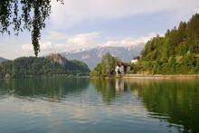 Krajobraz Słoweńskiego Miasteczka Bled, Jezioro, Promenada Wzdłuż Brzegu Z Piękną Zabudową, Ufortyfikowana Budowla Na Skalistym Wzniesieniu, W Tle Alpy Julijskie Z Ośnieżonymi Szczytami