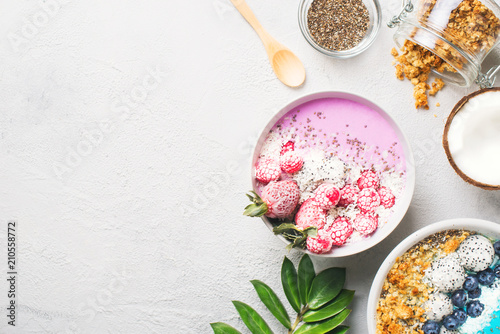 Pink and blue smoothie in bowl with pitaya, strawberry and raspberry