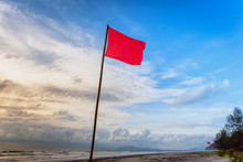 Red Warning Flag At Beach.Swimming Is Dangerous In Ocean Waves. Red Warning Flag Flapping In The Wind On Beach At Stormy Weather Phuket, Thailand.