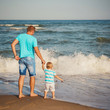 Young father with small son walking at beach together near the ocean, happy lifestyle family concept. Back view