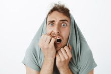 Indoor Shot Of Funny Scared Caucasian Guy With Bristle, Pulling T-shirt On Head And Staring With Popped Eyes Through Collar, Biting Fingernails, Trempling From Fear And Being Afraid Over Gray Wall