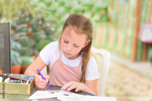 Little girl painting at table in summer garden  Cute child