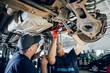Car mechanics repair car suspension of lifted automobile at repair service station