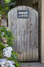 Arched Rustic Wooden Door To Steps And Garden With Beware Of Dog Sign