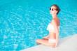 young beautiful woman in white bikini relaxing in spa pool