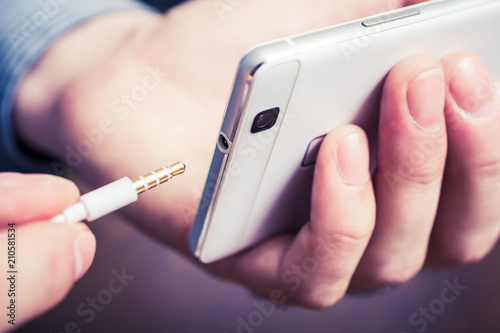 Photo Headphone Jack Of A White Smartphone Gets Plugged In