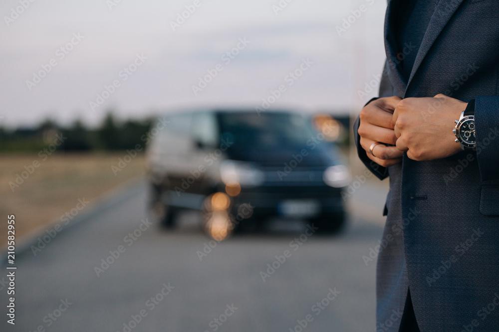 Fototapeta Man in suit stay in front of luxury car minivan