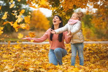 Cheerful Girls Playing With Yellow Leaves. Happy Mother And Little Child In The Fall Time Having Fun