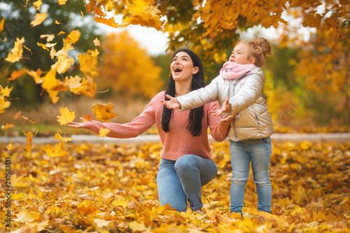 Obraz Cheerful girls playing with yellow leaves. Happy mother and little child in the fall time having fun - fototapety do salonu