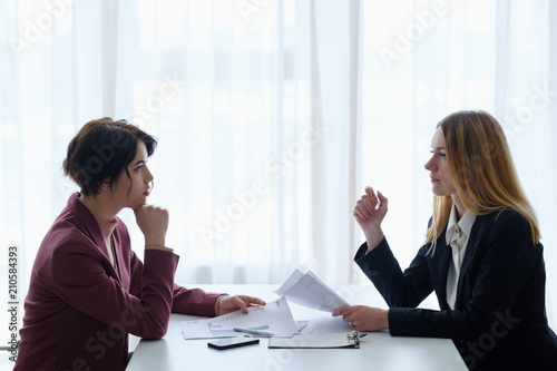 business negotiation communication. two women confronting each other in boarding room. office workspace