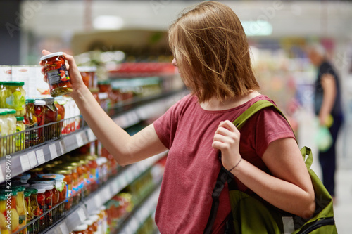 Fotografía  Sideways shot of pretty young femake customer holds canned goods in glass contai