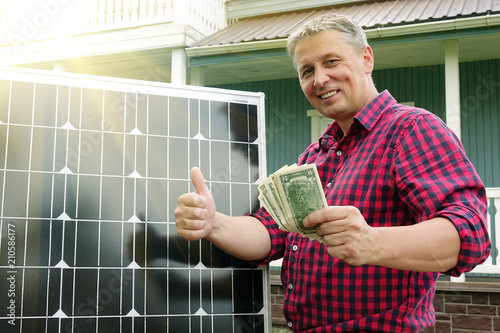 Solar panel. Money in the hands of men . Energy production technologies. Wooden house background. Saving.