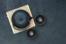 Black  Teapot And Tea Cups On Stone Table